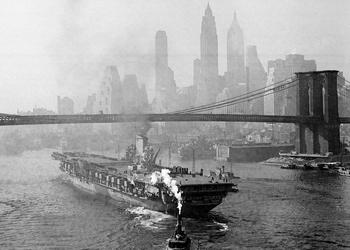 Tugs escort a ship from the Brooklyn Navy Yard